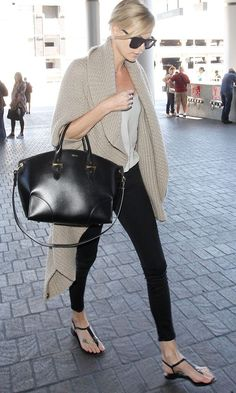 Charlize Theron in a beige cardigan, white top, black pants, bag and sandals.