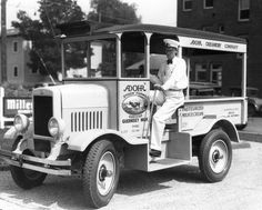 1931 - A Milkman for Adohr Creamery Company, sits at the wheel of his delivery truck.
