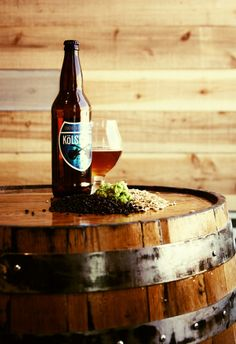 Photo taken in Coachella Valley Brewing Company's tasting room of beer bottle and glass on a barrel.