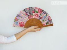 Abanico de madera y tejido de algodón japonés en colores lila y rosa con detalles dorados.