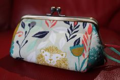 Cosmetic bag with metral frame and cotton fabric. Real leather strips give an accent on the bag.