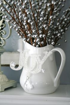 "Blue, Green, White and Silver Christmas Decorating Ideas. Per the creator, ""These silver berries were purchased at Hobby Lobby at 50% off.. making them .50 cents each...along with the ""joy"" ornament, that ended up being $1.20. And I found the white pitcher at Tai Pan Trading, for $2.97."""