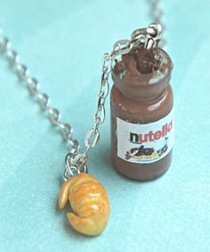 this necklace features a miniature glass jar of nutella spread along with a mini croissant charm. the choco hazelnut spread is made from some liquid clay and polymer clay. both charms are attached to