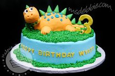 "Cake Walk: Fun Dinosaur Cake   ""...molded a dinosaur out of Rice Krispies Treats and covered it with fondant. I covered him with teal polka dots and gave him a yellow collar. Green fondant spikes lined his back, from the top of his head to the end of his tail. The cake itself was iced in blue buttercream and accented with green buttercream grass."""