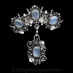 A lovely sterling silver pin and/or pendant featuring four shimmering moonstones presented in an elaborate floral and foliate motif. Wonderful age appropriate oxidation on the silver.