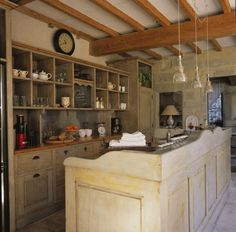 3/3 pic of this kitchen. Wooden island with beautiful curves, behind open upper shelves and closed lower shelves, notice heart and clove cut out in drawer, 3 pendant lamps, small table lamp with shade same color as wall, one side of wall made of stones, floor looks like stone tiles