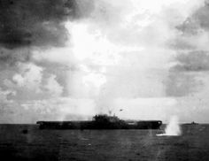 A Japanese Nakajima B5N2 Kate torpedo aircraft (visible just above and to the right of carrier's island) drops a torpedo (splash at lower right) that will hit the U.S. Navy aircraft carrier USS Hornet (CV-8) and cause fatal damage on 26 October 1942.