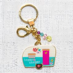 "Glitter & Gold Key Chains Happy Camper - Resin-poured Glitter & Gold ""Happy Camper"" keychain features metal token with glitter and bead embellishments. Includes key ring and clip."