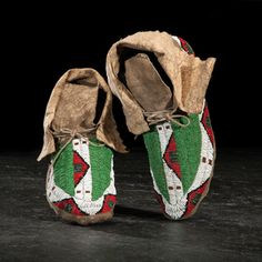 Assiniboine Beaded Hide Moccasins from the Monroe Kily (1910-2010) Collection sinew-sewn and beaded using colors of red, green, white, black, and amber; folded cuffs with pinked edges, length 9.5 in. early 20th century Provenance: Property of a Minnesota Collector; Ex Monroe Killy (1910-2010) Collection Price Realized Including Buyer's Premium $420 09/23/2016