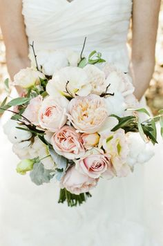 The bridesmaids' bouquets will be blush garden roses, blush garden spray roses, white cotton, gray dusty miller, white lisianthus, and small accents of olive leaves wrapped in soft gold ribbon with the stems showing.