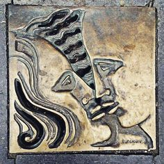 Hatch in urban asphalt road pavement (Brussels) #brussels #hatch #road #artwork #asphaltroad #art #kiss #feelings #feeling #bronze