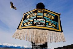 Photo of Native Alaskan wearing a Chilkat Blanket while looking upward at a soaring Bald Eagle in Alaska. Composite