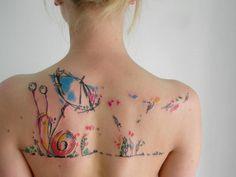 caracol tatuado en la espalda al estilo acuarela
