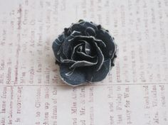 Why throw a bottle cap in the trash when you can make it into a beautiful pin! Dark Denim Rose with White Writing Bottlecap Brooch Pin by VioletVox, $4.00
