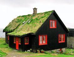 casita negra con ventanas rojas