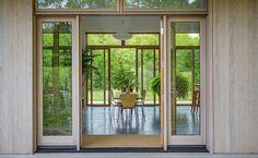 Portas deslizantes de vidro oferecem vista desobstruída da porta da frente ao grande jardim.  Fotografia: Trevor Tondro / The New York Times.