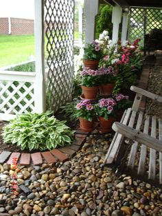Under-the-deck space. Pretty trellises. Pebbles and brick edging are nice together.