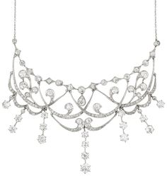 An Edwardian Diamond Necklace. The front designed as a garland motif, each swagged line set with old-cut diamonds, suspending a graduated old-cut diamond fringe, mounted in platinum and 14K yellow gold, length 16 1/2 inches.