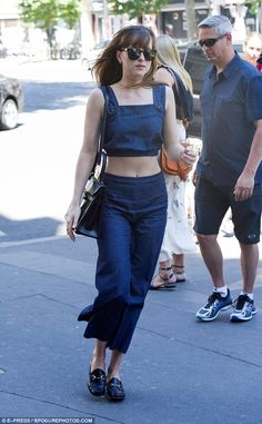 Abs-olutely fabulous! Flashing a glimpse of her toned abs, Dakota opted for a chambray crop top with thick button straps whilst her defined arms were on display
