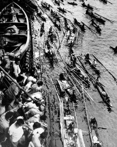 Native outrigger canoes approach a Coast Guard troop transport.  The Moros have come for two purposes:  to trade their souvenirs and to dive for coins thrown into the sea by Coast Guard crew members and GI's. Philippines, ca. 1945.