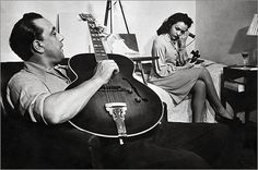 Django Reinhardt playing a Gibson ES300 guitar as an unidentified woman looks on. c. 1945