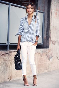 Julie Sariñana of Sincerely Jules wears a blue and white striped button-down shirt with distressed white jeans, nude sandals, a silver watch, and a black leather bag