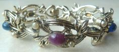 A Vintage faux pearl and mock gemstone panel bracelet by Jewelcraft The bracelet is formed from gold tone metal with five panels Each panel is formed