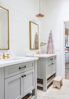 double light grey vanities in bathroom with gold hardware and mirrors