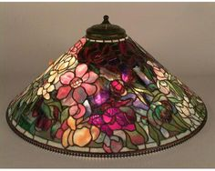 "ca. 1900-1906 ARTIST/MAKER:Tiffany Studios . (73.7 × 30.5 cm) DESCRIPTION Leaded glass and bronze Peony hanging lamp; 28"" diameter cone-shaped shade depicting bouquet of flowers using highly textured glass and thick chunks of colored glass for the flower centers; flower colors include red, yellow, white and pink using undulating, rippled, and fibrillated glass; borders of grayish blue glass around aperture and lower rim; metal beading at top and bottom of shade."