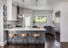 HGTV: See this contemporary country kitchen with gray and white cabinets and a chevron tile backsplash.