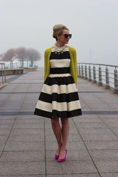 Bold black and white dress, chunky statement necklace, and bright sweater with bright contrasting heels!