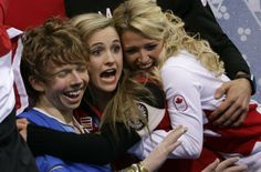 SOCHI, Russia – Canada has captured its fourth medal at the Sochi Olympics. The figure skating team won silver at the first-ever Olympic team figure skating competition. Kevin Reynolds of Canada, left, and team members react as he sits in the results area after competing in the men's team free skate figure skating competition at the Iceberg Skating Palace during the 2014 Winter Olympics, Sunday, Feb. 9, 2014, in Sochi, Russia.