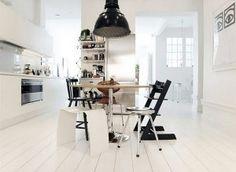Keuken met witte vloer. Dit is een goed exemplaar van een witte vloer in het interieur. Het contrast tussen de witte vloer en de zwarte elementen werkt goed omdat er alleen een paar donkere elementen zijn en wit nog steeds overheerst. Het totaalbeeld blijft licht.
