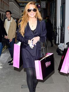 Lindsay Lohan, flaunting cool aviator sunnies, was all smiles as she shopped around London with lots of purchases in tow!