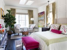 The master bedroom with an elegant sitting area, inviting queen size bed, lots of natural light and pops of hot pink provides the perfect space for relaxing and resting in luxury.