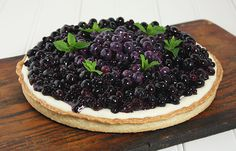 Close up photo of a Blueberry Mascarpone Tart decorated with sprigs of fresh mint displayed on a dark wooden board.