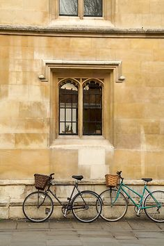 Two bicycles with baskets rest against the sandstone wall of Corpus Christi College on Trumpington Street, Cambridge UK. It was founded in 1352.