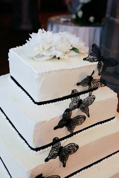 white square four tier wedding cake with black borders and black butterfly decor with a white floral top - photo by Italian wedding photographer JoAnne Dunn