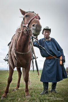 Portrait of a man and his horse in Mongolia.