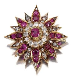 RUBY AND DIAMOND BROOCH/PENDANT, LATE 19TH CENTURY.  Designed as a sixteen pointed star, centring on a pinched collet-set cushion-shaped ruby, within a border of circular-cut diamonds, further decorated with variously-shaped rubies, accented with circular- and rose-cut diamonds, pendant loop fitting.