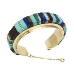 This elegant Charles Loloma 14k gold bracelet is beautifully inlayed with turquoise, lapis, ironwood, coral, and malachite.  Measures 5 1/4″ with a 1 1/8″ opening.  1″ width.  The 1 3/4″ safety chain can be removed.