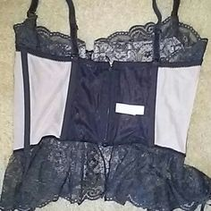 Victoria Secret corset Very cute black Lacey with one a nude color behind the lace. Has a cute ribbon tie front. Zip and little clip closure above zipper. Has a cute red bow on back right side. Adjustable straps. Has a couple tiny pick marks on the inside as shown. Outside like good. Very nice shape still. Victoria's Secret Intimates & Sleepwear Chemises & Slips