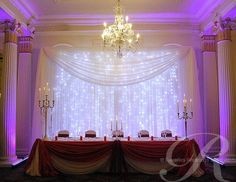 Red head table draping with fairy light backdrop.