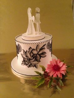 Hand painted Lace wedding cake 		Royal iced cake, brush embroidery, lace piping, line work,piped bride and groom.   Accompanied by flowerpaste a Gerbera spray. ~ all edible