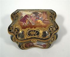 Sevres style gilt decorated cobalt ground porcelain casket<z> <br  />  <br  /> 19th century<z> <br  />  <br  /> Scallop form, the lid painted to show an 18th-century lady choosing wallpaper, within an acanthus, C-scroll and trellis border, opening to a silk lined cushioned interior, the body painted to show four landscapes within gilt reserves, underglaze blue interlaced mark to underside. <br  />  <br  /> H: 4 1/2, W: 9, D: 7 in. <br  />  <br  />