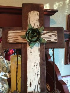 Reclaimed wood cross with a Shabby Chic flair. 1st layer of wood is from a flat wine stave. 2nd layer is from reclaimed fence wood left in it's rustic white patina. Large metal rose is hand cut.