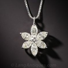 Six rays of starlight, or flower petals, each composed of a sparkling marquise-cut diamond, shines bright and radiate outward from a single round brilliant-cut diamond, all of which total 1.54 carats, in this gorgeous, glittering platinum and diamond pendant, measuring 3/4 inch. A bargain priced beauty.