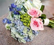 This soft and sweet bouquet is made of pink and white roses, blue hydrangeas and darker blue sweet peas.