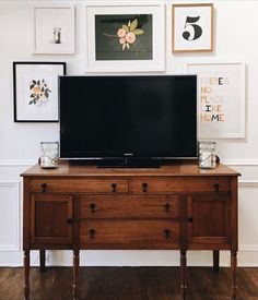 Gallery wall behind tv and showing that even an antique cabinet can make a stunning place to put your tv on