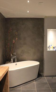 Prachtige badkamer met beton cire muren, vrijstaand bad en wastafel van oude vloerbalken
